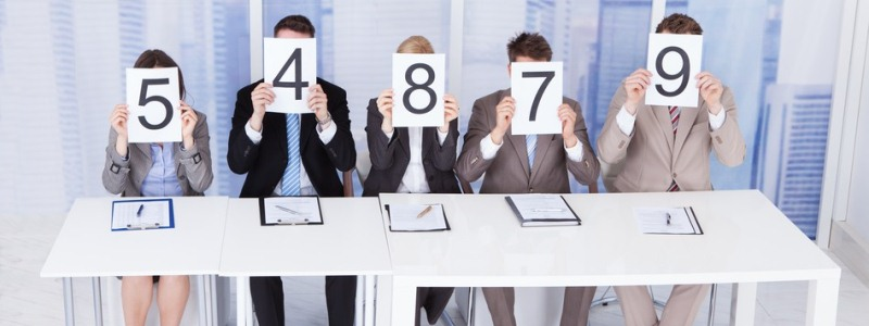 Portrait of confident business people showing score cards